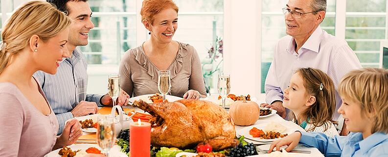 Family at Thanksgiving Dinner. Closets and Cabinetry offers tips on Holiday home organization.