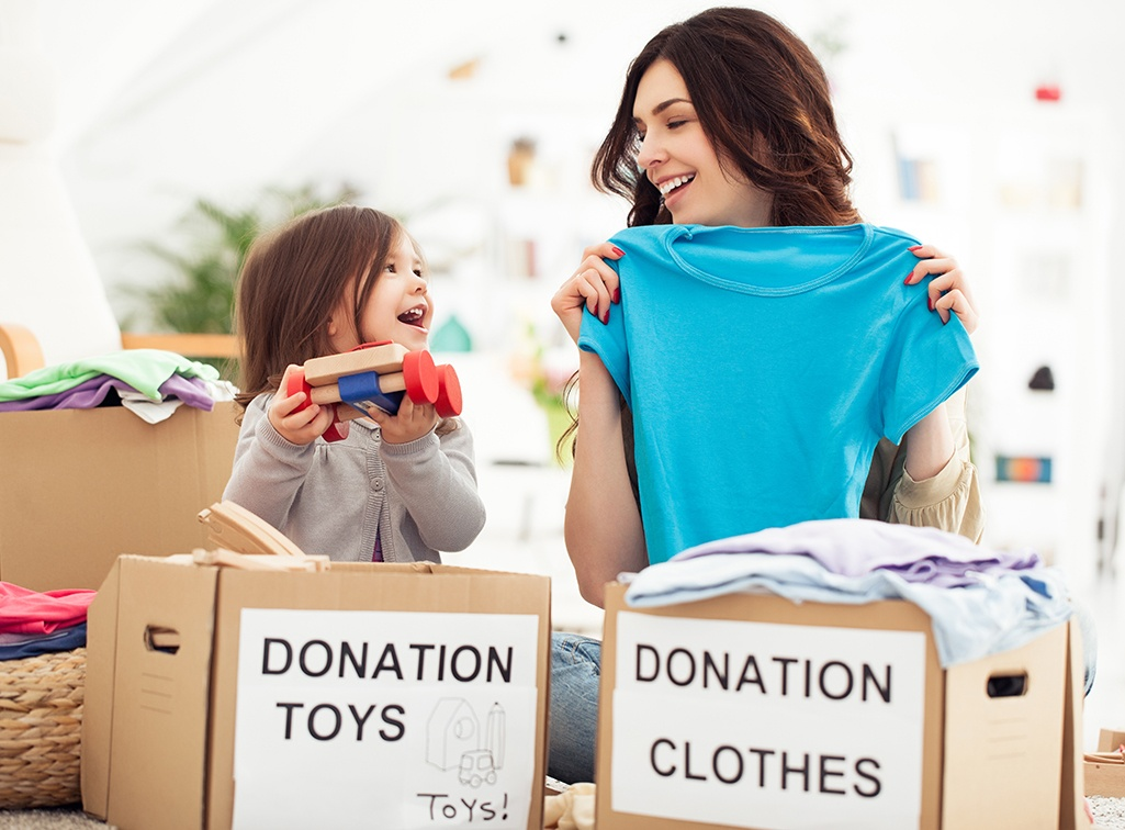 Mom and duaghter collecting toys and clothing for donating.