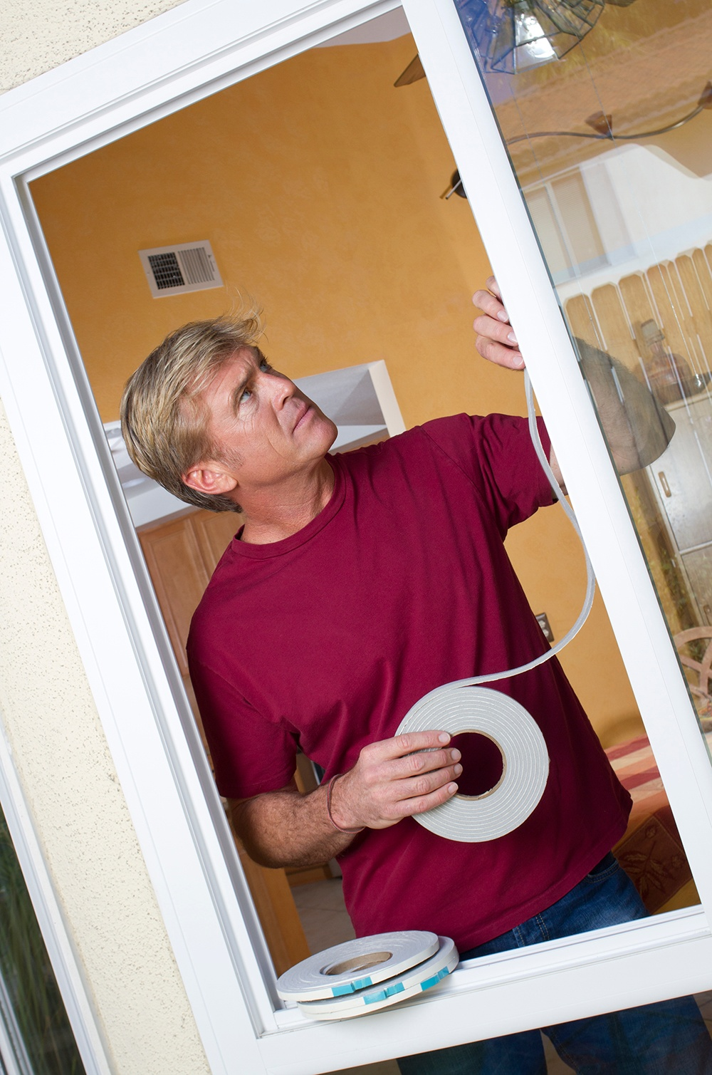 Man weather stripping a window. Weather stripping is a great way to save energy.