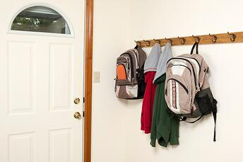 Coat rack by the door for kids to hang their coats and backpacks