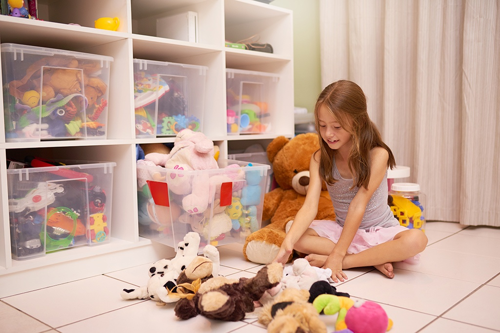 Girl playing with her toys in a clean space with toys in storage boxes.