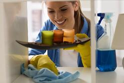 woman cleaning shelf. Before decorating for the holiday clean off dust from all your shelves.