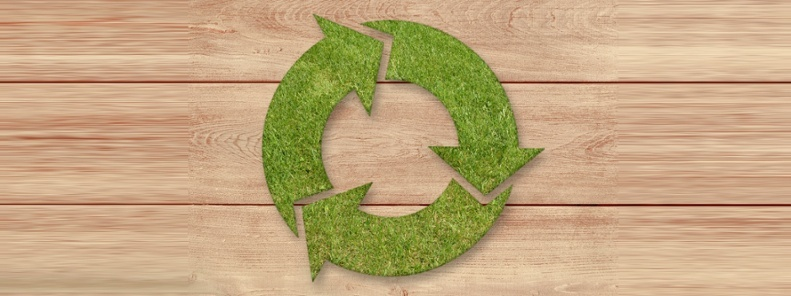 Recycle symbol made out of grass on wood surface