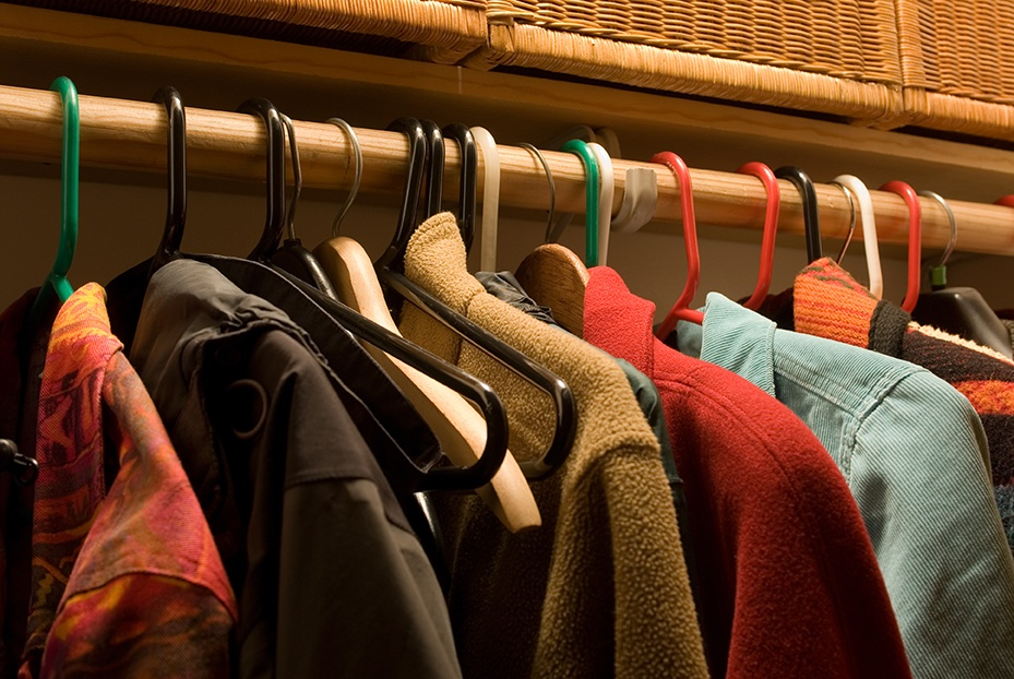 Coats hanging in closet . One way to organize your home for the holidays is to make sure you have plenty of space for guest winter coats.